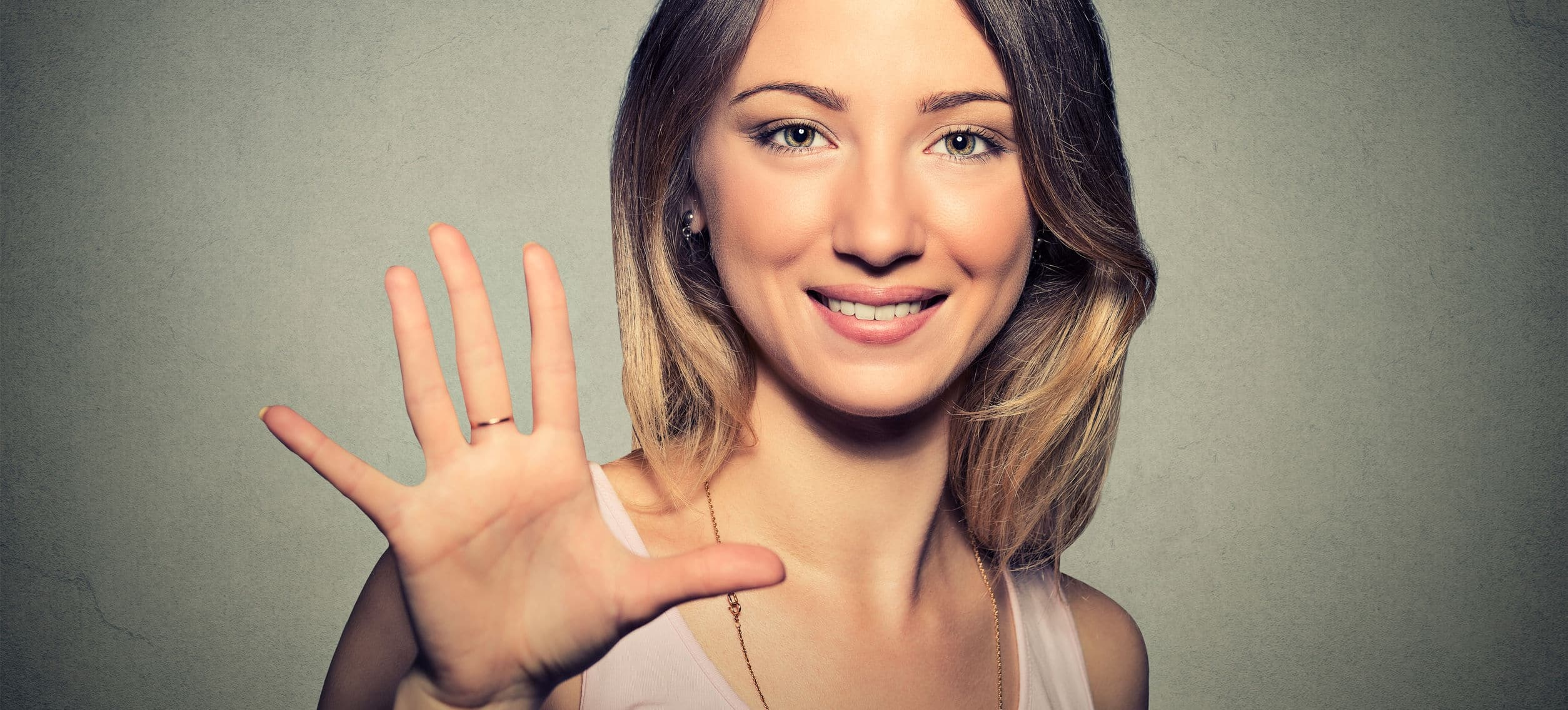 Smiling woman holding up five fingers