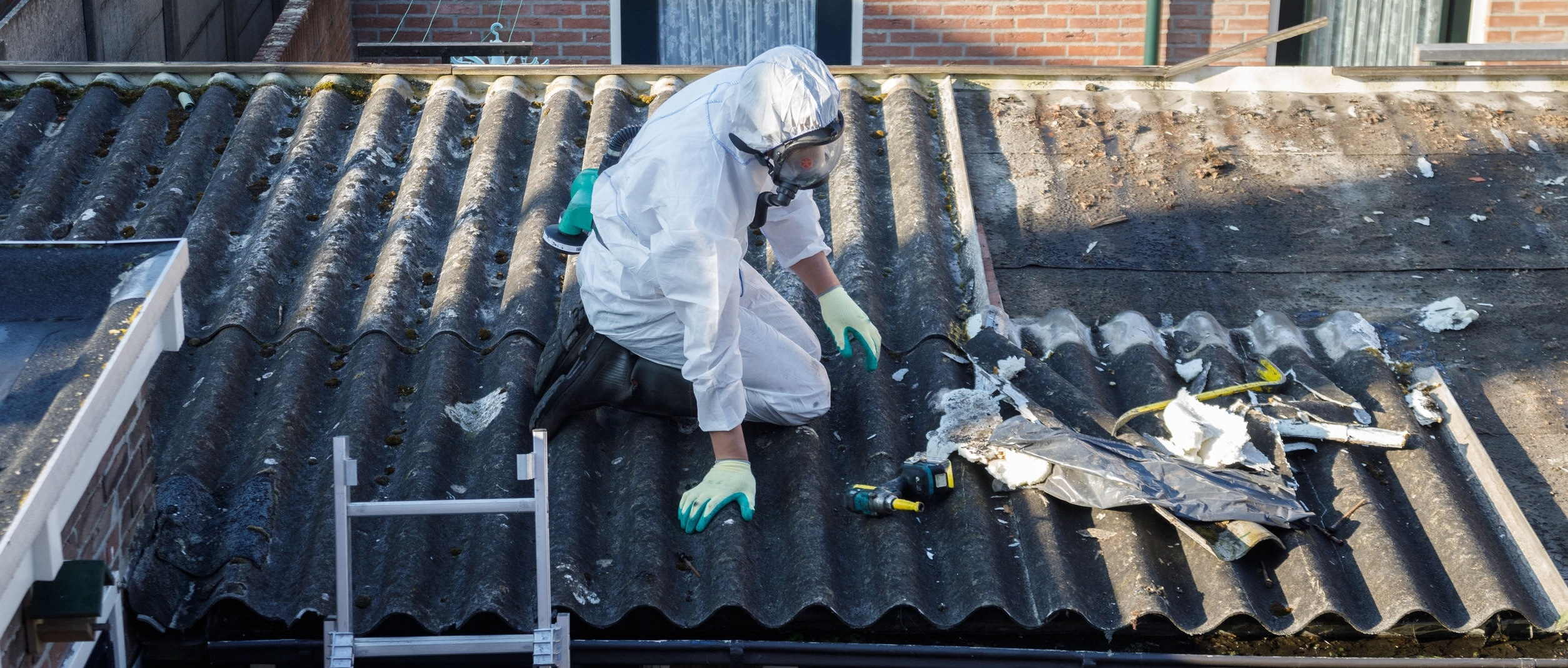 Men in protective suits are removing asbestos cement corrugated roofing