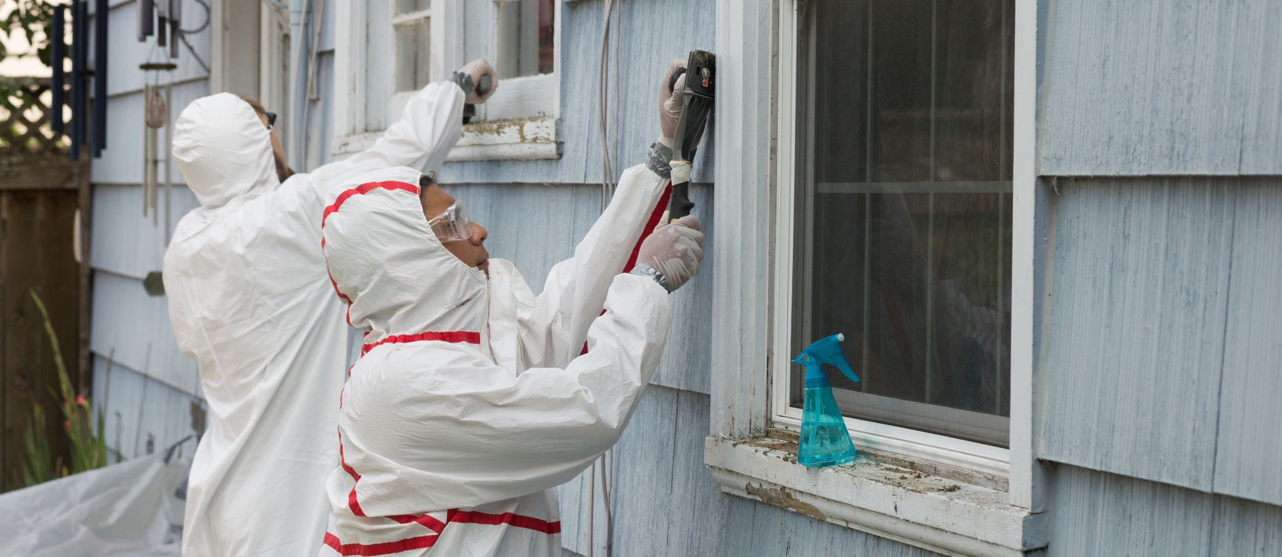 Two house painters in hazmat suits removing lead paint from an old house